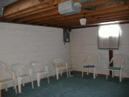 basement with ample seating for weekly a a meetings space heater and